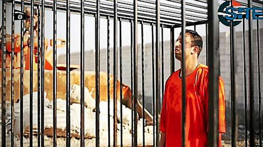 This still image made from video released by Islamic State group militants and posted on the website of the SITE Intelligence Group on Tuesday, Feb. 3, 2015, purportedly shows Jordanian pilot Lt. Muath al-Kaseasbeh standing in a cage just before being burned to death by his captors. The death of the 26-year-old pilot, who fell into the hands of the militants in December when his Jordanian F-16 crashed near Raqqa, Syria, followed a weeklong drama over a possible prisoner exchange. (AP Photo/SITE Intelligence Group) Photo: AP / SITE Intelligence Group