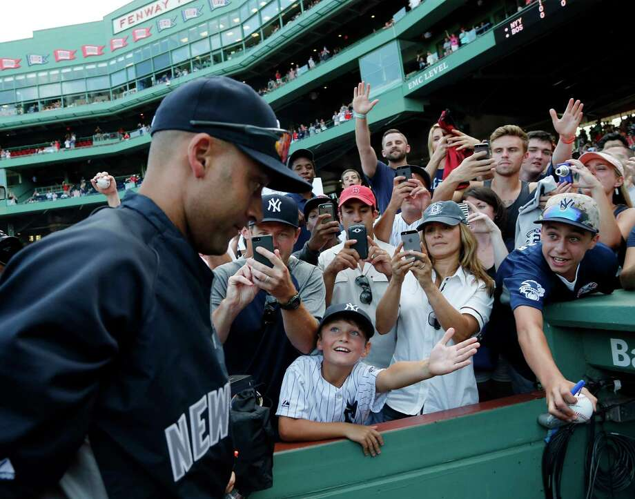 Fans greet New York Yankees shortstop Derek Jeter as he leaves the field after the final game of his career against the Boston Red Sox on Sunday at Fenway Park in Boston. Photo: Elise Amendola — The Associated Press  / AP