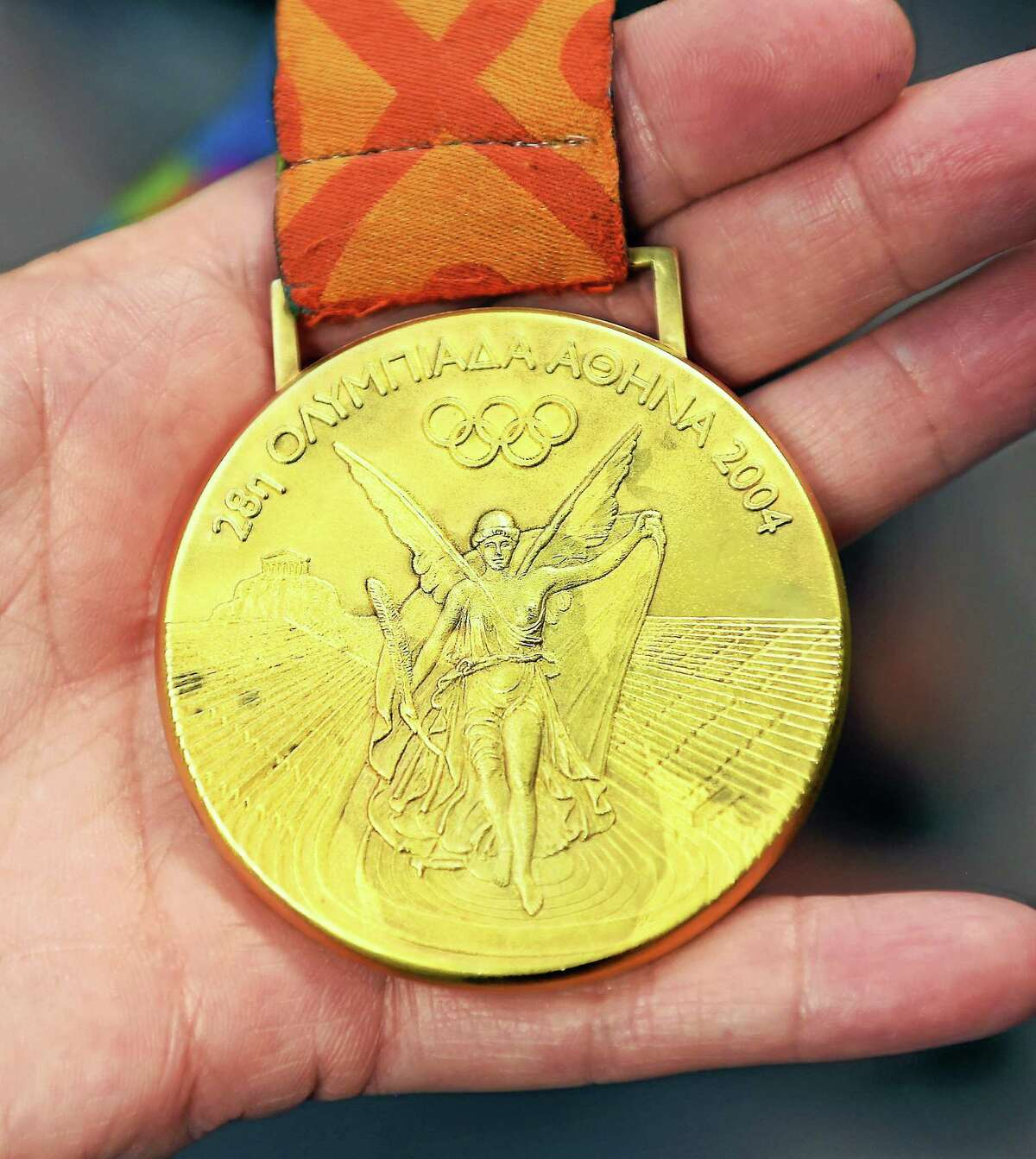 An employee of Liberty Mutual Insurance views former U.S. Olympic soccer player Brandi Chastain's gold medal from the 2004 Athens Olympics during a visit to the Wallingford Liberty Mutual Insurance on Wednesday.