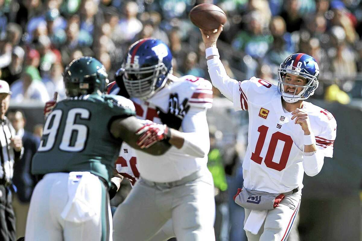 New York Giants quarterback Eli Manning (10) throws a pass as Will Beatty (65) blocks the Eagles' Bennie Logan (96) during a 2013 game in Philadelphia.