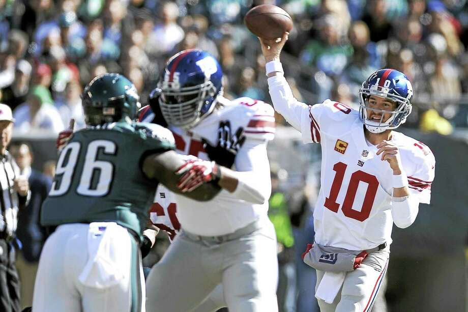 New York Giants quarterback Eli Manning (10) throws a pass as Will Beatty (65) blocks the Eagles' Bennie Logan (96) during a 2013 game in Philadelphia. Photo: Michael Perez — The Associated Press File Photo  / AP2013