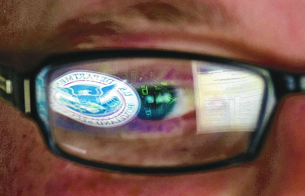 This Sept. 30, 2011, file photo shows a reflection of the Department of Homeland Security logo in the eyeglasses of a cybersecurity analyst at the watch and warning center of the Department of Homeland Security's secretive cyber defense facility in Idaho Falls, Idaho.
