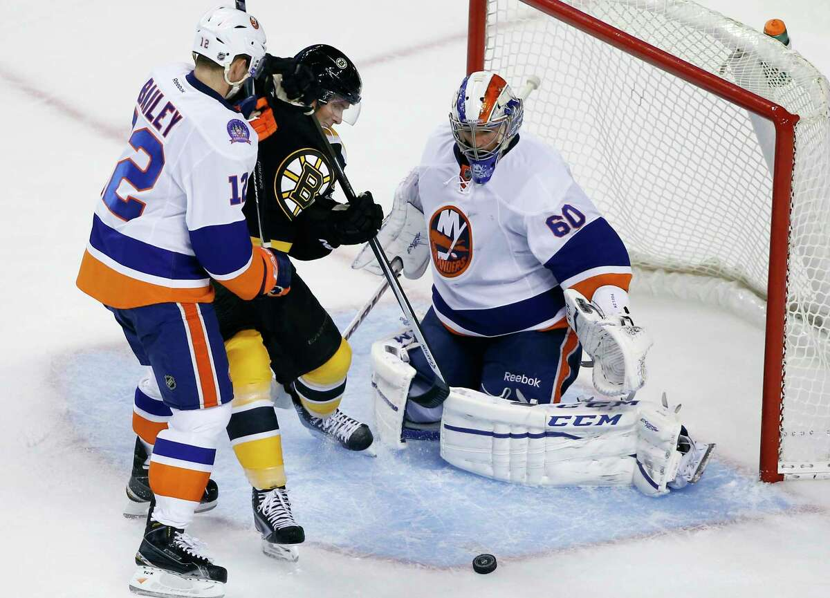 New York Islanders left wing Josh Bailey (12) prevents Bruins left wing Loui Eriksson from getting to the puck in the crease as goalie Kevin Poulin (60) protects the net during a preseason game on Tuesday in Boston.