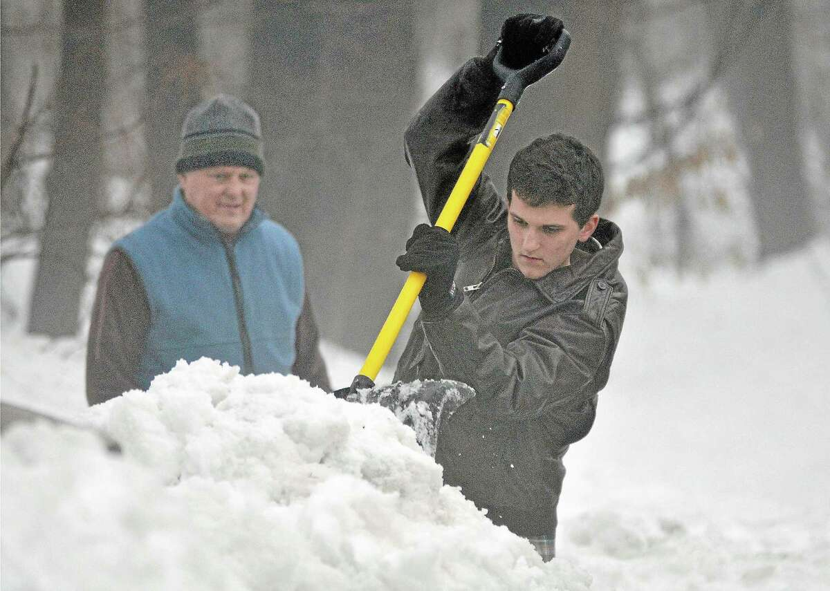 Durham resident Liam Bialobrzeski chips away the snow surrounding a mailbox in this file photo. Cromwell police are urging motorists to use extra care when driving because of high snow banks which limit visibility.