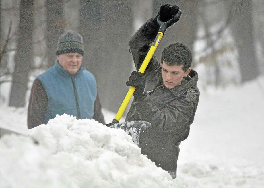 Durham resident Liam Bialobrzeski chips away the snow surrounding a mailbox in this file photo. Cromwell police are urging motorists to use extra care when driving because of high snow banks which limit visibility. Photo: File Photo  / TheMiddletownPress