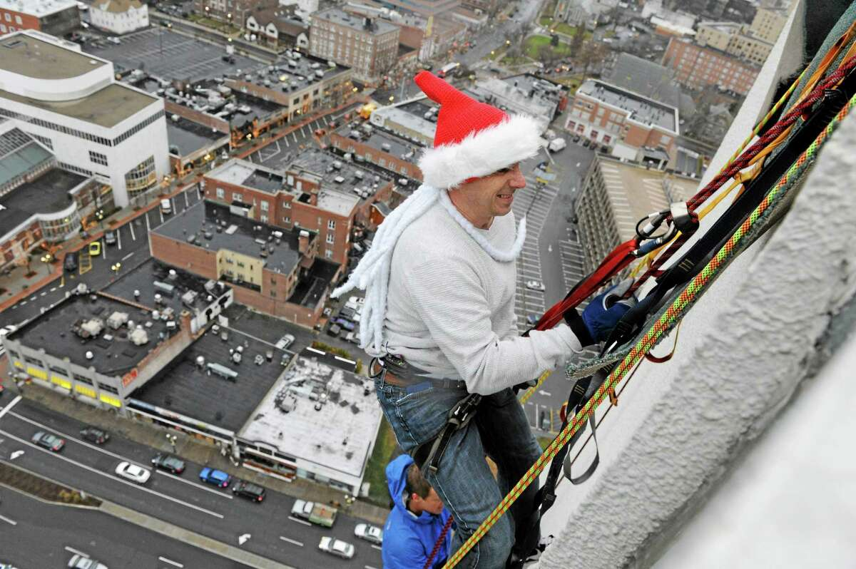 New York Yankees general manager Brian Cashman rappels down One Landmark Square during a charity event on Dec. 6, 2013, in Stamford.