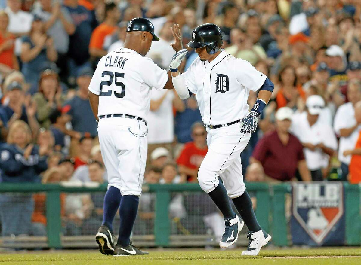Detroit Tigers' Victor Martinez is congratulated by third base coach Dave Clark (25) after hitting a solo home run against the Boston Red Sox in the eighth inning of a baseball game in Detroit, Friday, June 6, 2014. (AP Photo/Paul Sancya)