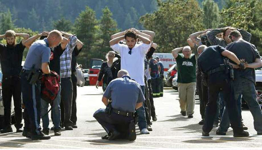 Police search students outside Umpqua Community College in Roseburg, Ore., Thursday, Oct. 1, 2015, following a deadly shooting at the college. Photo: (Mike Sullivan/Roseburg News-Review Via AP) / Roseburg News-Review