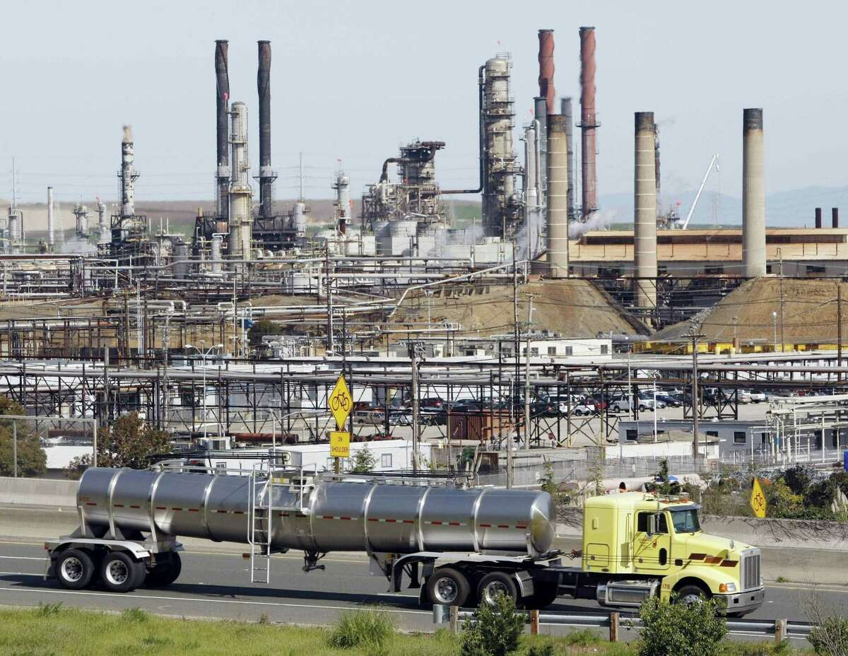 In this March 9, 2010 photo, a tanker truck passes an oil refinery in Richmond, Calif.