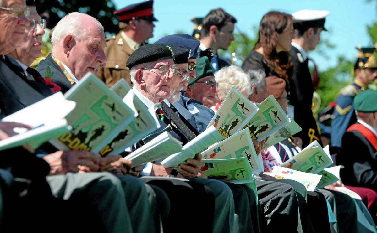 British veterans and other participants attend a French-British D-Day commemoration ceremony at the British War Cemetery in Bayeux, France, Friday, June 6, 2014. World leaders and veterans gathered by the beaches of Normandy on Friday to mark the 70th anniversary of World War Two's D-Day landings. (AP Photo/Thomas Bregardis, Pool)