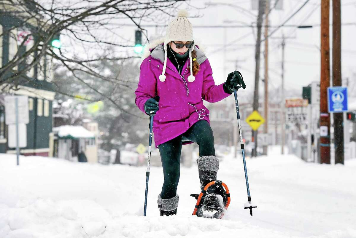 Rachel Schwartzman snow shoes on Broad St. in Milford Monday morning 2/2/2015. Her work opening was delayed until noon.