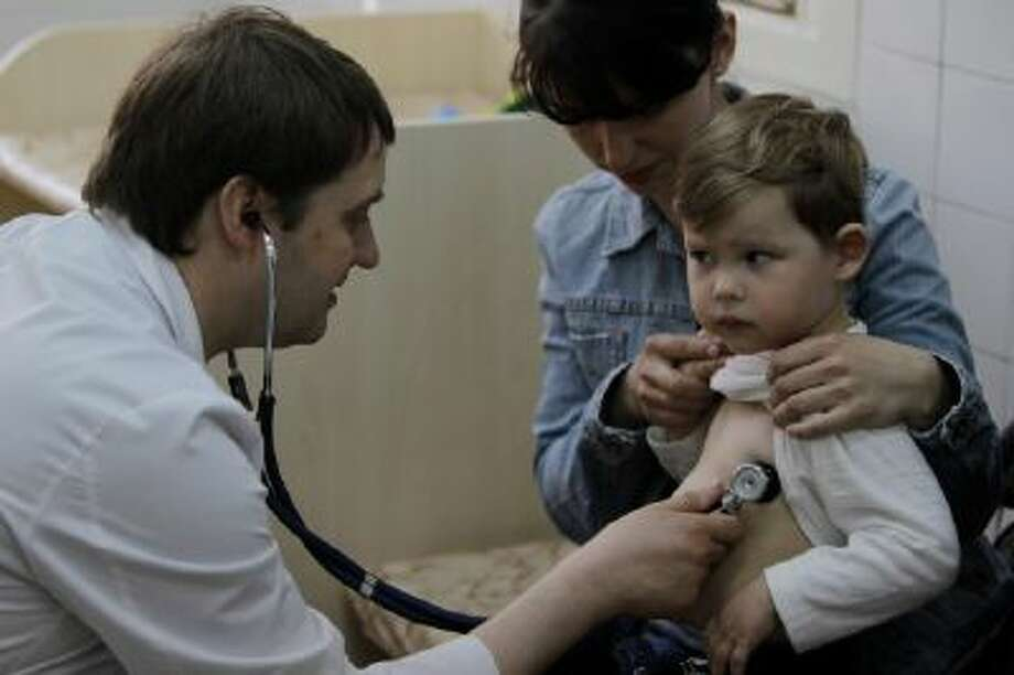 Pediatrician Fyodor Lapiy examines a child before administering him a combined vaccine against diphtheria, whopping cough and tetanus.