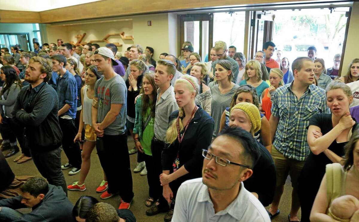 People stand in the foyer during a prayer service at the First Free Methodist Church Thursday, June 5, 2014 at Seattle Pacific University in Seattle, where a shooting took place Thursday afternoon.(AP Photo/Ted S. Warren)