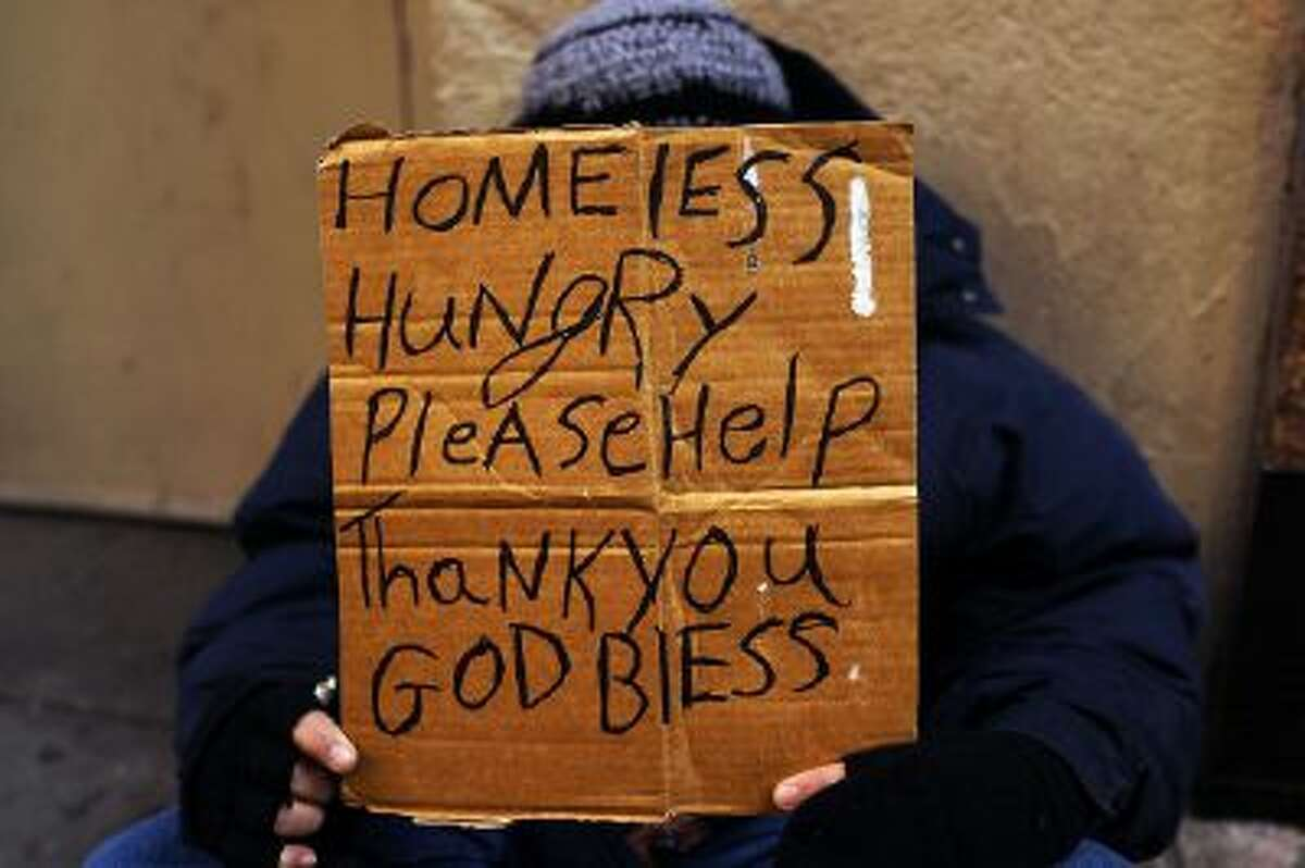 A person holds a sign asking for money in New York City in December. The government's official measure of poverty doesn't catch everyone.