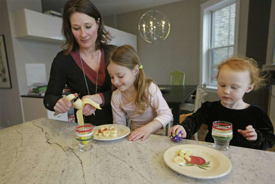 Kathy Burnett prepares a snack for her daughters Claudia, center, and Sabina right, after their gymnastics class Thursday, Jan. 29, 2015, in Chicago. Burnett says she tries to feed her girls healthy, natural foods rather than commercial packaged products. Photo: AP Photo/M. Spencer Green  / AP