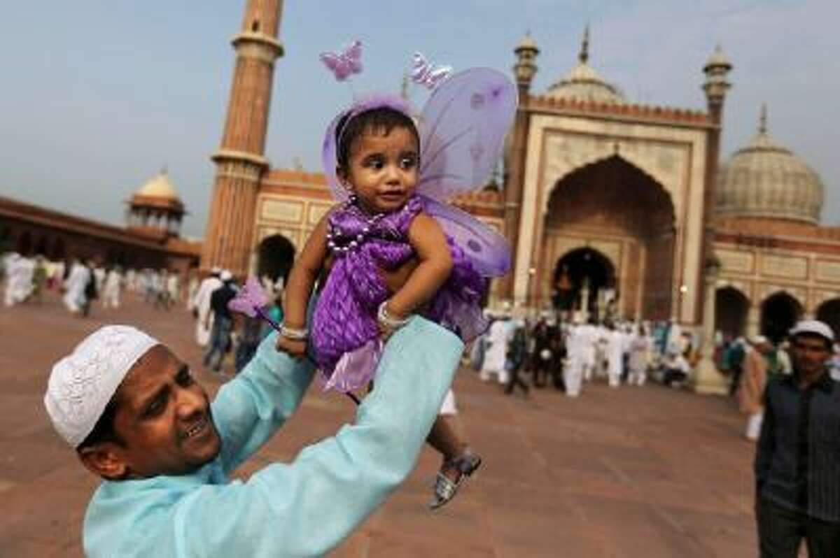 An Indian Muslim man holds up his daughter after Eid al-Fitr prayers at the Jama Masjid in New Delhi, India.