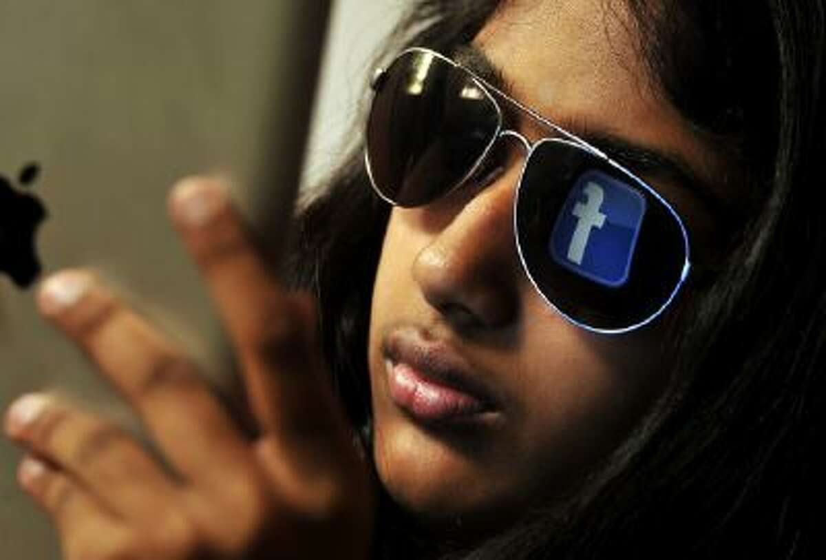 The 'Facebook' logo is reflected in a young Indian woman's sunglasses as she browses on a tablet in Bangalore on May 15, 2012.