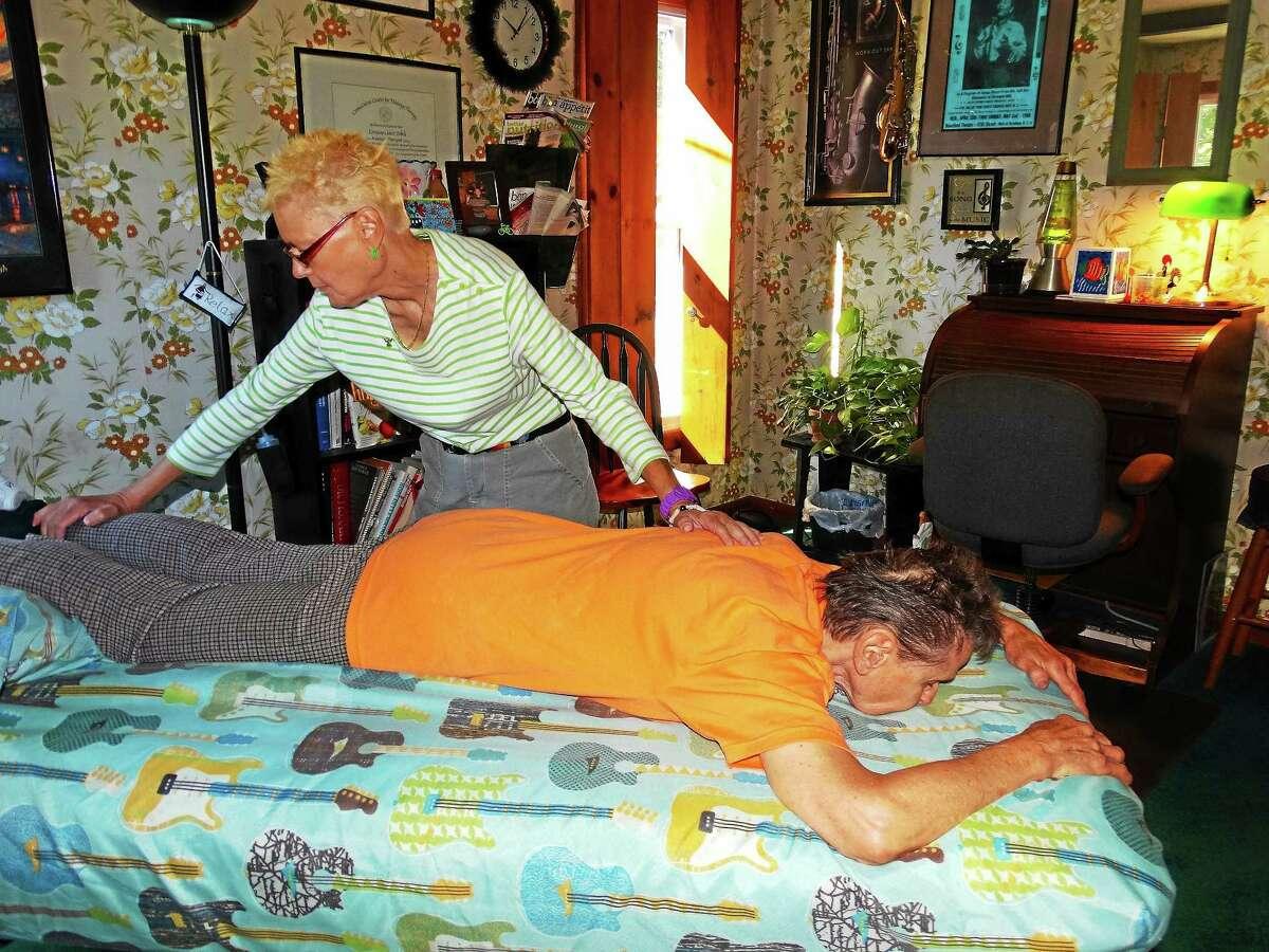 Middletown massage therapist Lorraine Dobek helps a client.