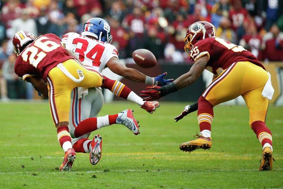 Washington inside linebacker Perry Riley (56) intercepts an Eli Manning pass intended for running back Shane Vereen on Sunday. Photo: Alex Brandon — The Associated Press  / AP