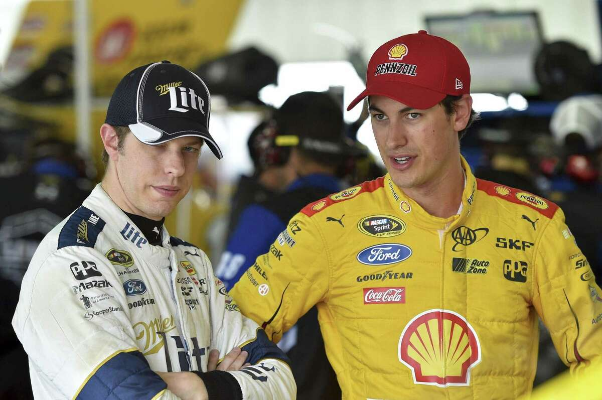 Brad Keselowski, left, stands with Joey Logano in the garage area at Pocono Raceway Friday in Long Pond, Pa.