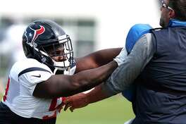 Houston Texans defensive tackle D.J. Reader, left, hits a blocking pad held by defensive coordinator Mike Vrabel during training camp at The Greenbrier on Saturday, Aug. 12, 2017, in White Sulphur Springs, W.Va.