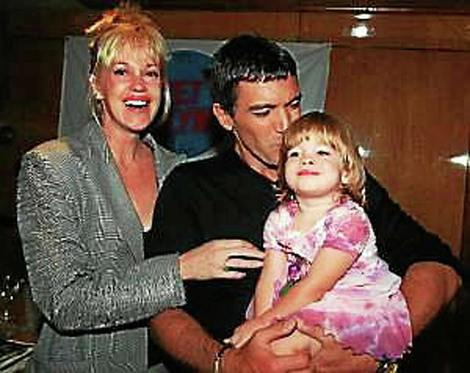 Melanie Griffith laughs as Antonio Banderas kisses their daughter Stella at Planet Hollywood Wednesday, July 15, 1998, in New York. Photo: (Anders Krusberg — The Associated Press)