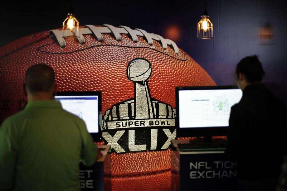 A mural of a football decorates the wall of an Super Bowl XLIX ticket office as customers check for seating availability on Saturday in Phoenix. Photo: David Goldman — The Associated Press  / AP