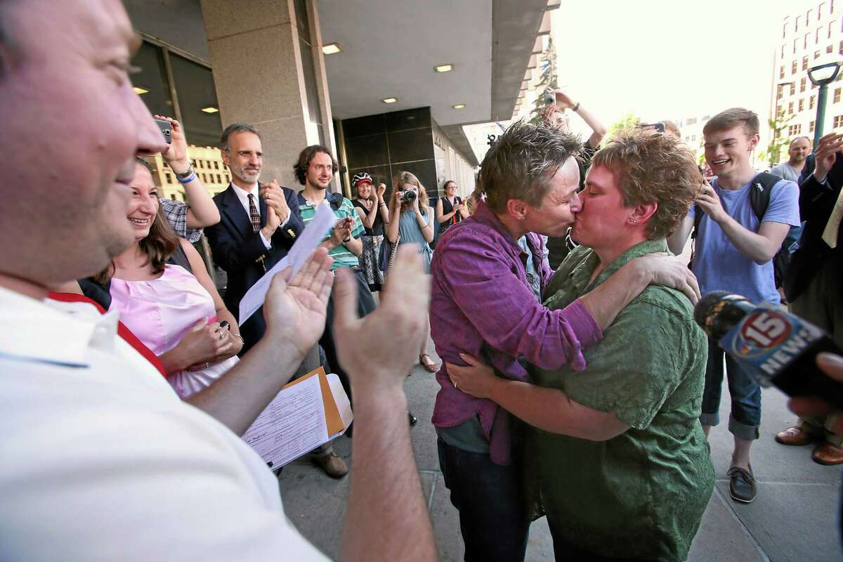 Shari Roll, left, and Renee Currie, of Madison, Wis., kiss as they were married by officiant Mike Quito on the steps of the City-County Building on Friday, June 6, 2014, in Madison, Wis., after a federal judge struck down a ban on same-sex marriage in the state. The couple have had a civil union for 10 years and have been together since 2003.