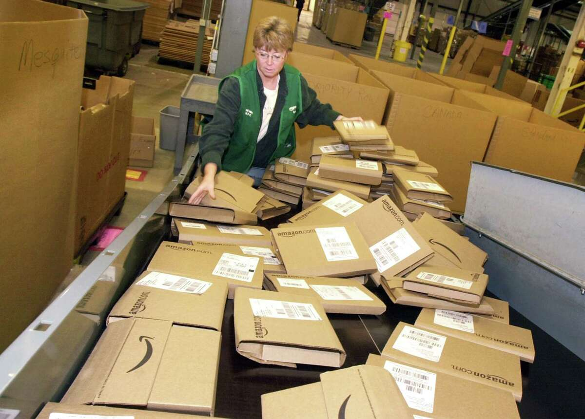 In this Nov. 13, 2002, photo, an Amazon employee sorts through orders ready to be shipped from its Coffeyville, Kansas, warehouse.