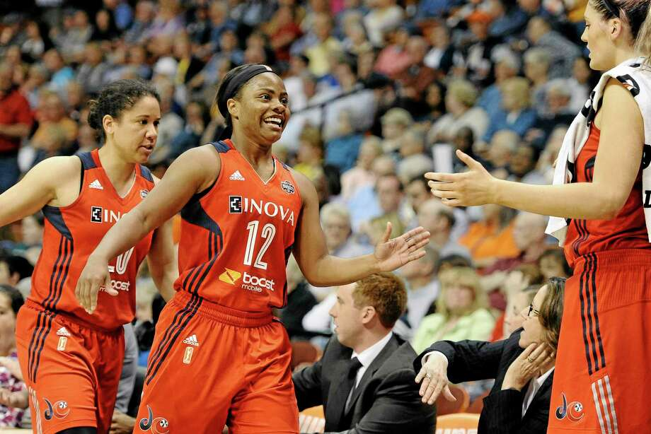 Washington Mystics' Ivory Latta, center, and teammate Kara Lawson, left, are greeted on bench by Stefanie Dolson during the second half Thursday. Photo: Jessica Hill — The Associated Press  / FR125654 AP