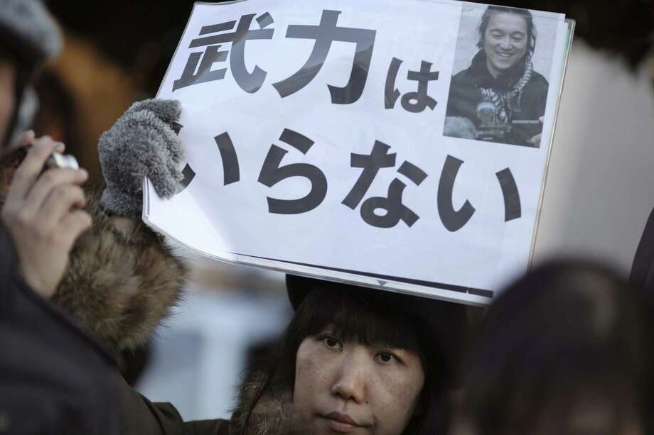 "A woman sympathizer for Japanese hostage Kenji Goto holds a sign stating: ""We do not need armed forces"" and bearing his photo in front of the prime minister's official residence in Tokyo on Feb. 1, 2015 after an online video purporting to show an Islamic State group militant beheading Goto was circulated via social media. Photo: AP Photo/Eugene Hoshiko  / AP"