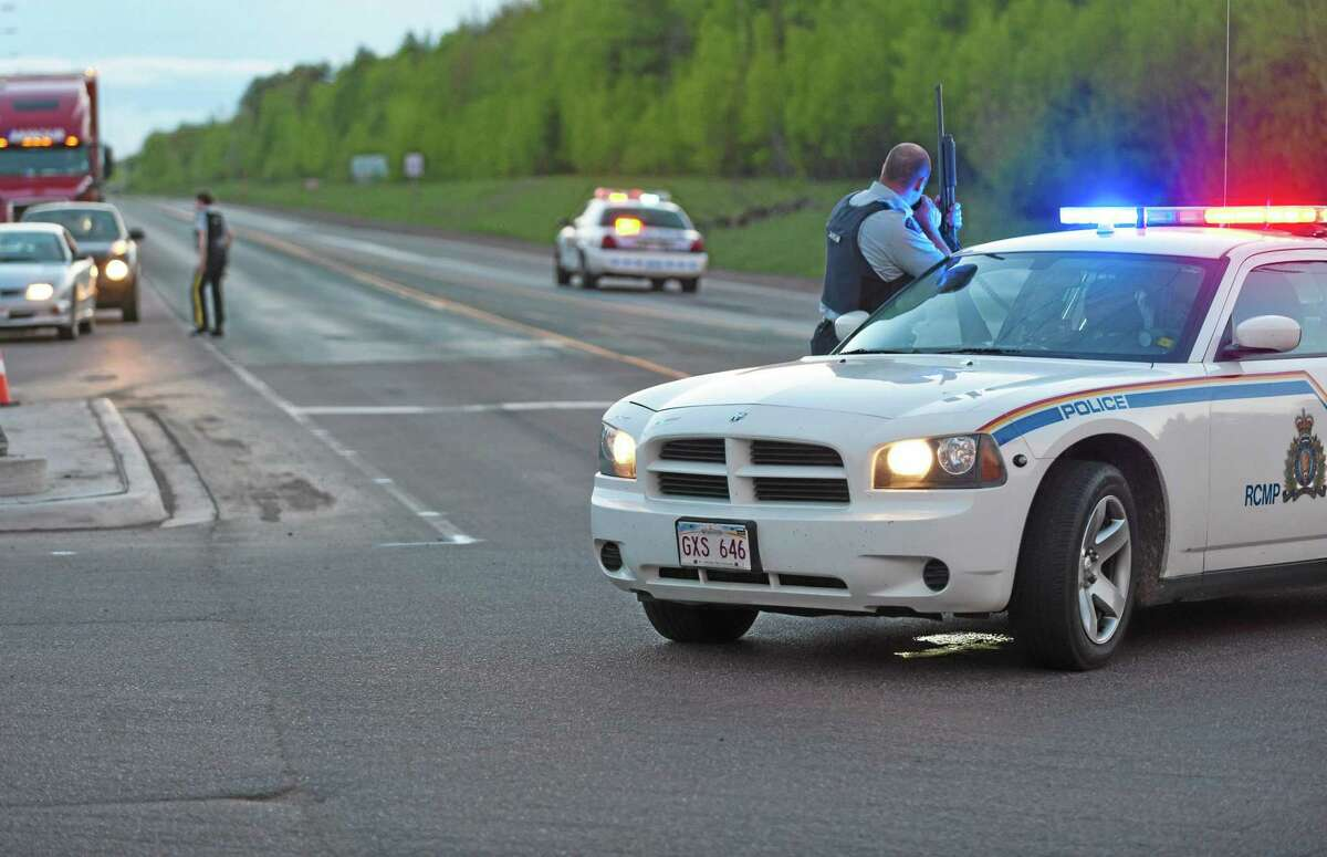 Royal Canadian Mounted Police officers use their vehicles to create a keep a perimeter in Moncton, New Brunswick on Wednesday June 4, 2014. The RCMP in New Brunswick said an undisclosed number of people have been shot and a manhunt is underway in the north end of Moncton for a man armed with guns.