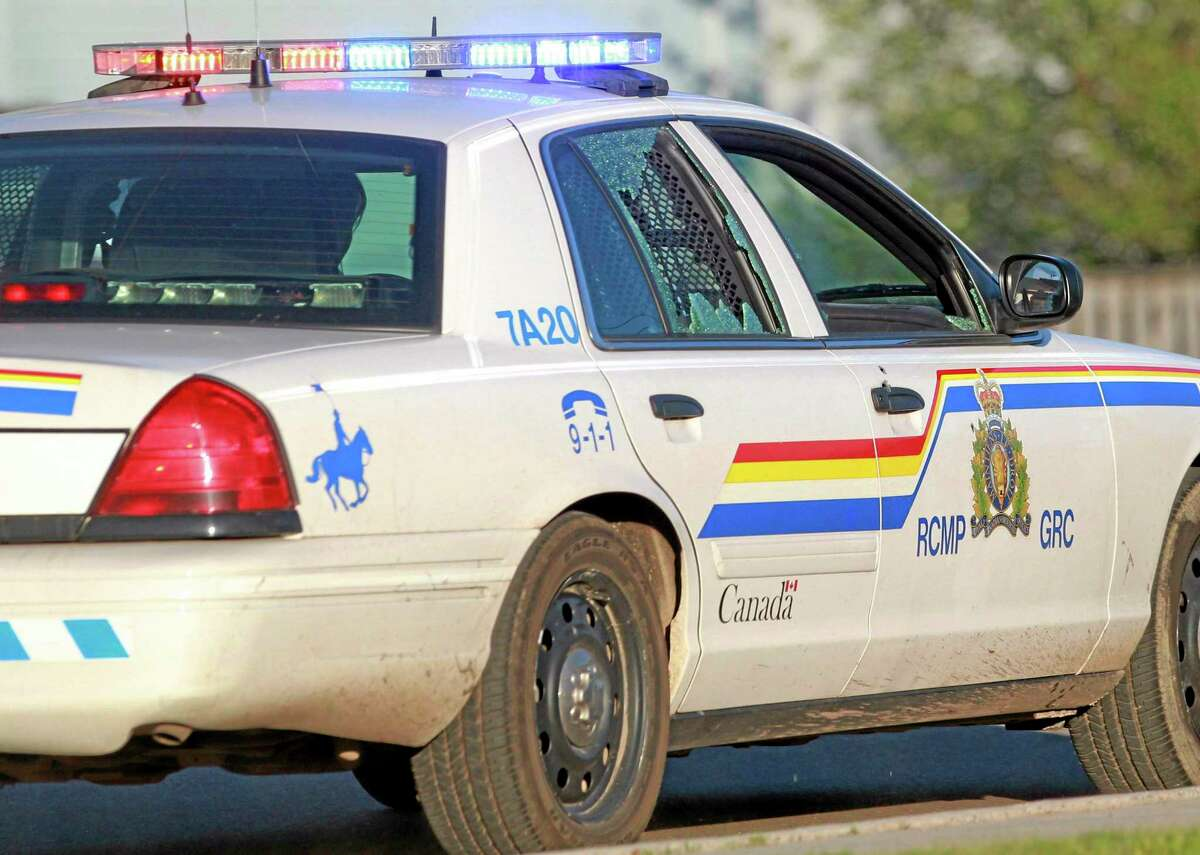 A Codiac Royal Canadian Mounted Police officer drives with the rear door window shattered by a bullet in Moncton, New Brunswick, on Wednesday, June 4, 2014. Three police officers were shot dead and two others injured Wednesday in the east coast Canadian province of New Brunswick, officials said, and authorities were searching for a suspect. The RCMP in New Brunswick confirmed on its Twitter feed that three officers were dead and two others had sustained non-life threatening injuries.
