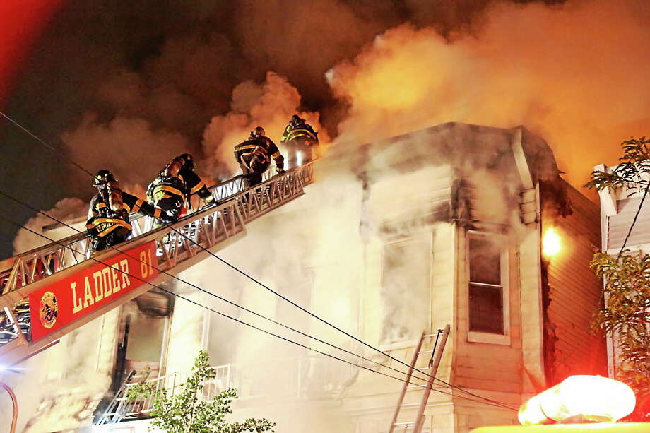 (AP Photo/Staten Island Advance, Ryan Lavis) Firefighters battle a fire that tore through three townhouses on New York City's Staten Island early Thursday, June 5, 2014. At least 34 people were injured, including two young children who were tossed out of a smoke-filled second-floor window into the arms of neighbors below, authorities and witnesses said. Photo: AP / AP2014