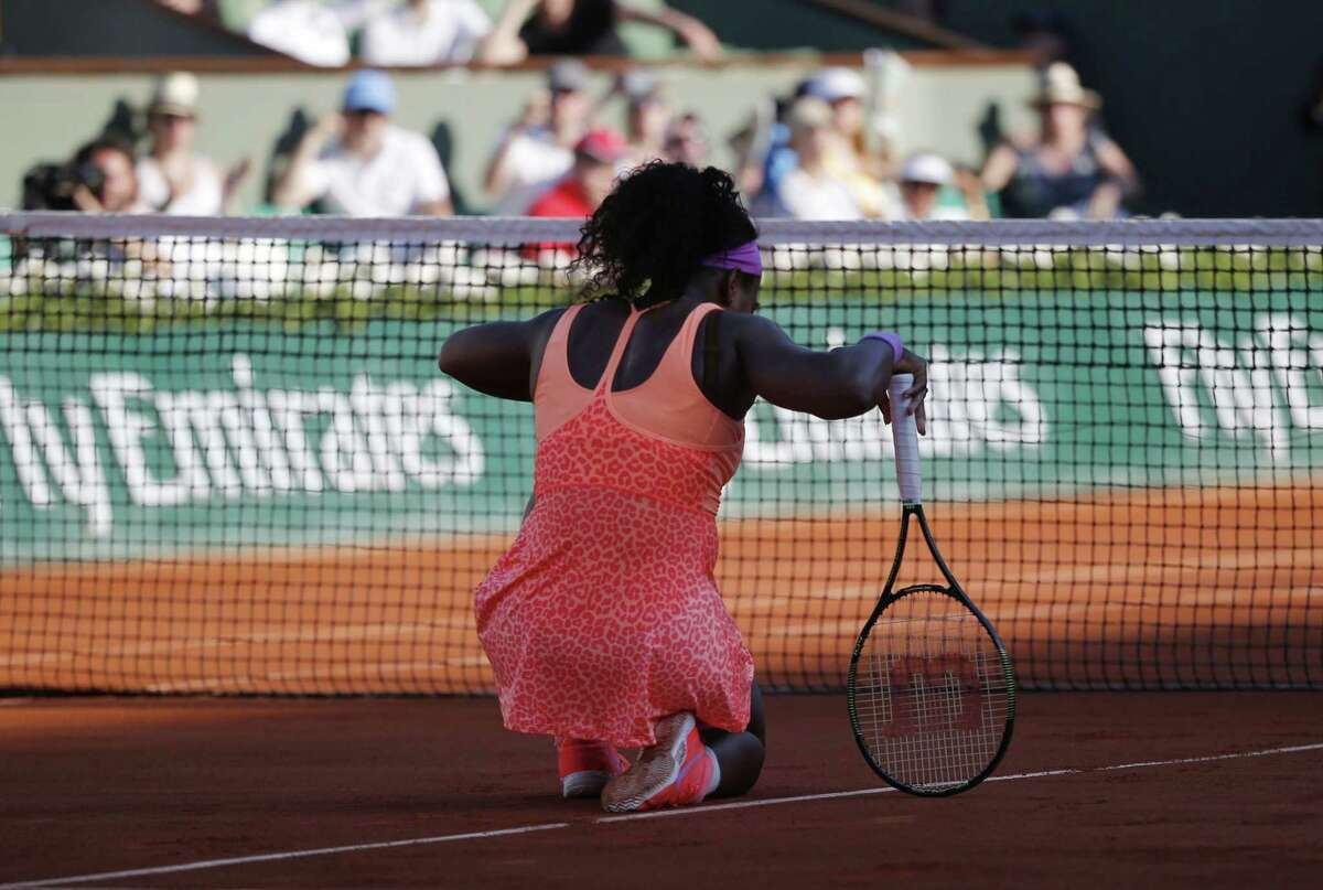 Serena Williams kneels at the net as she plays Timea Bacsinszky during their semifinal match at the French Open on Thursday at the Roland Garros stadium in Paris.