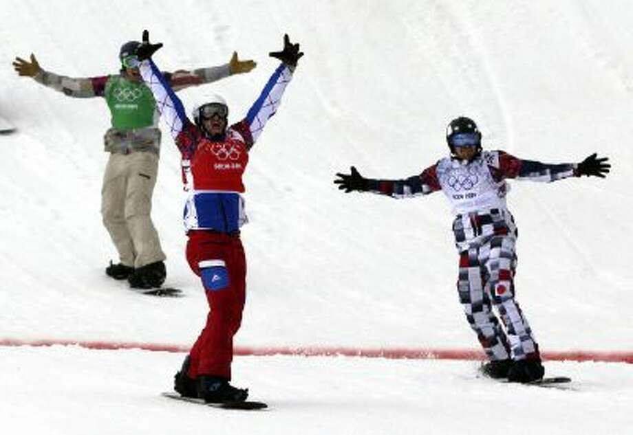 France's Pierre Vaultier, second left, celebrates taking the gold medal ahead of silver medalist Nikolai Olyunin of Russia, right, and bronze medalist Alex Deibold of the United States in the men's snowboard cross final at the Rosa Khutor Extreme Park, at the 2014 Winter Olympics, Tuesday, Feb. 18, 2014, in Krasnaya Polyana, Russia.