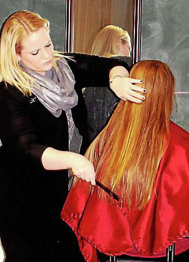 A stylist from The Cut Above hair salon in Cromwell shows a teen how to style her hair. A similar program, Decked out for December, at the library is offering tips for makeup, hair and dress for the upcoming holidays. Photo: Courtesy Photo