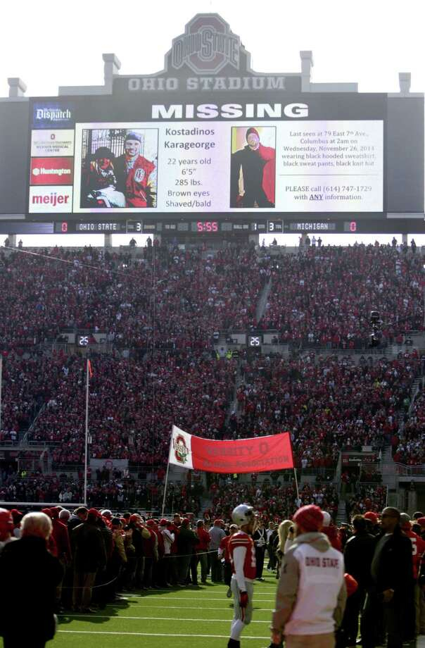 A police poster showing Kosta Karageorge, an Ohio State player who has been missing since earlier in the week, is displayed on the large video board at the south end of the field before the start of the Ohio State's game against Michigan Saturday. Photo: The Associated Press  / FR52593 AP