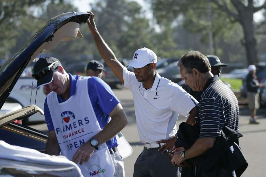 In this Feb. 5 file photo, Tiger Woods loads his car after withdrawing during the first round of the Farmers Insurance Open in San Diego. Photo: Gregory Bull — The Associated Press  / AP