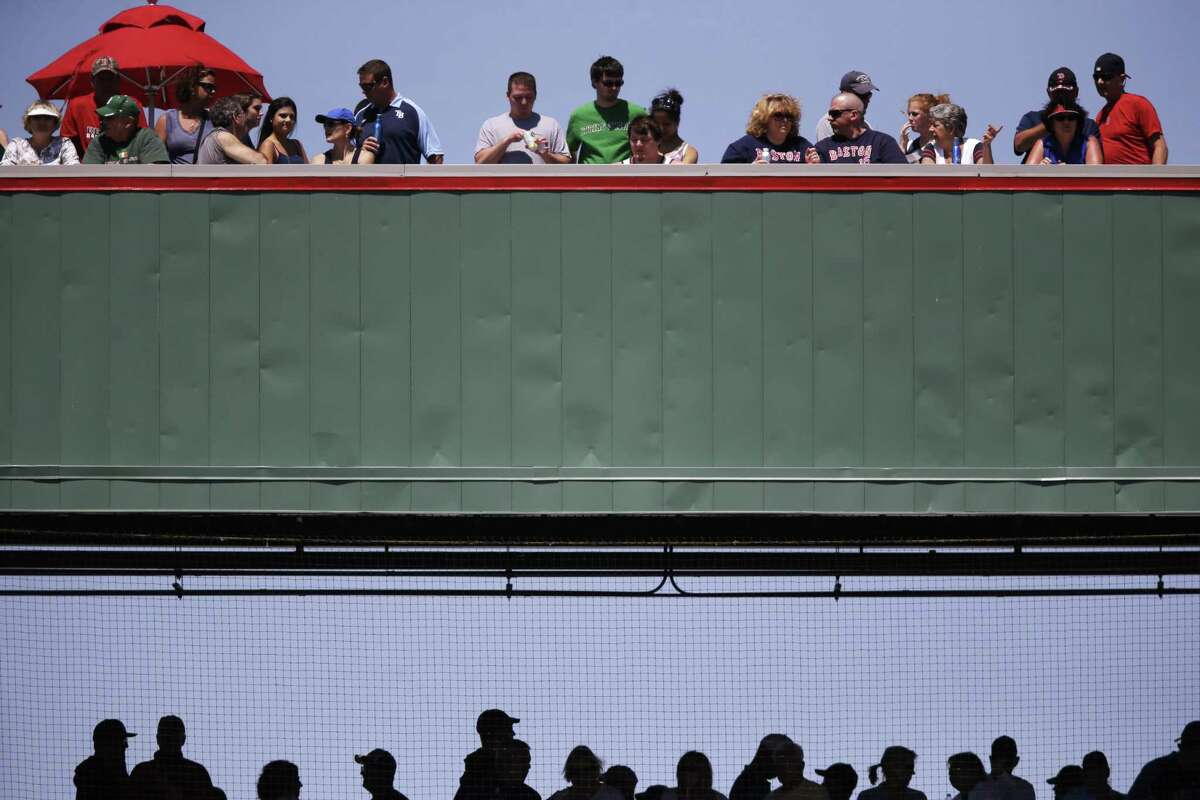 Fans watch a baseball game on the Green Monster replica at JetBlue park between the Tampa Bay Rays and the Boston Red Sox on Sunday in Fort Myers, Fla.