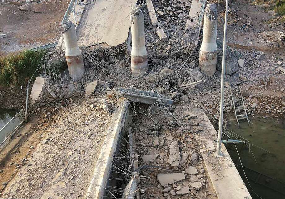This photo taken Wednesday, June 3, 2015, shows a destroyed bridge on the Euphrates river in northern Ramadi, Iraq. The Islamic State group destroyed the bridge with a car bomb to cut the northern entrance to the city, locals said. (AP Photo) Photo: AP / AP