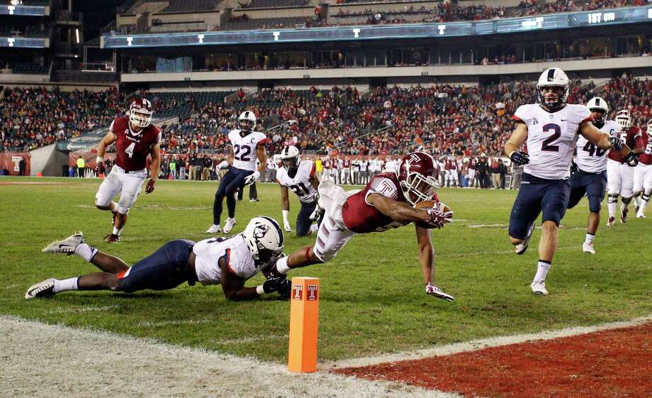 Temple running back Jahad Thomas, center, dives for the touchdown as UConn linebacker Junior Joseph, left, tries to stop him with linebacker Graham Stewart during the first half Saturday in Philadelphia. Photo: Chris Szagola — The Associated Press  / FR170982 AP