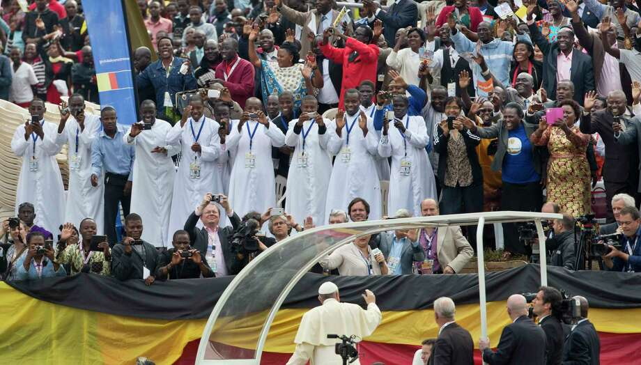 Members of the audience cheer and take photographs with their smartphones as Pope Francis, below, drives around the venue before leading a Holy Mass for the Martyrs of Uganda at the area of the Catholic Sanctuary in the Namugongo area of Kampala, Uganda Saturday, Nov. 28, 2015. Pope Francis is in Uganda on his first-ever trip to Africa, a six-day pilgrimage that has already taken him to Kenya and then onwards to the Central African Republic. Photo: AP Photo/Ben Curtis   / AP