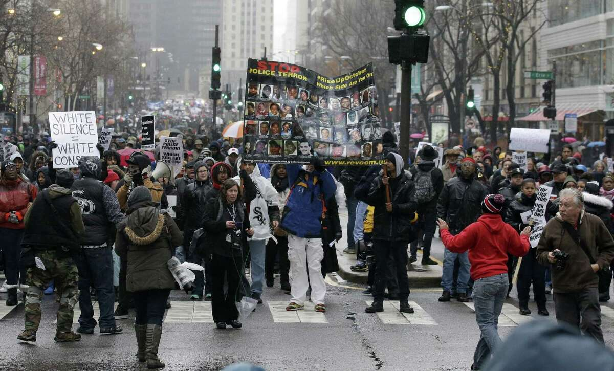 """Protesters make their way up North Michigan Avenue on Friday, Nov. 27, 2015, in Chicago as community activists and labor leaders hold a demonstration billed as a """"march for justice"""" in the wake of the release of video showing an officer fatally shooting Laquan McDonald."""