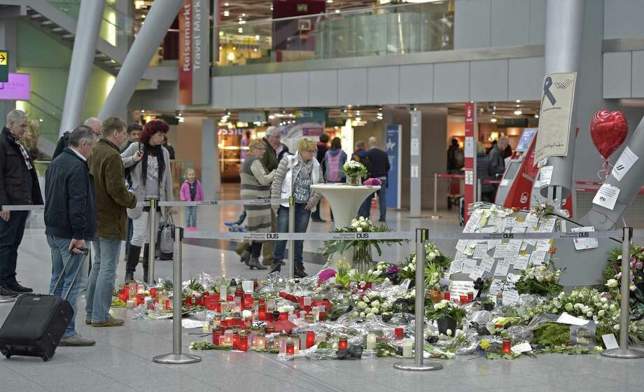 Passengers watch candles and flowers for the victims of the plane crash at the airport in Dusseldorf , Germany on March 31, 2015. One week ago 150 people died in the Germanwings airliner crash in the French alps from Barcelona to Duesseldorf. Photo: AP Photo/Martin Meissner  / AP