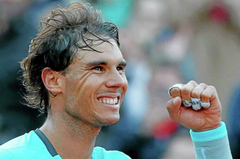 Rafael Nadal celebrates winning the quarterfinal match of the French Open against David Ferrer on Wednesday at the Roland Garros stadium in Paris. Nadal won 4-6, 6-4, 6-0, 6-1. Photo: Michel Euler — The Associated Press  / AP
