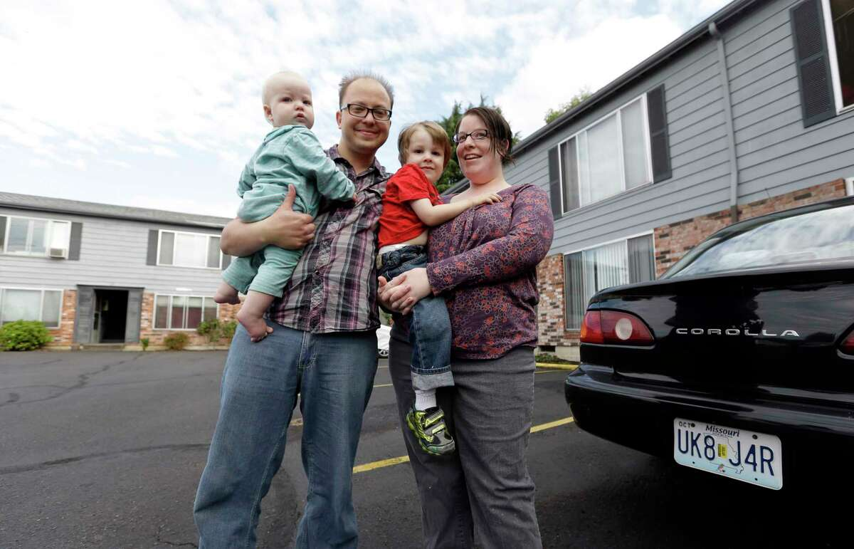 Steven and Nola Olsen pose in front of their apartment building with their children, Aubrielle, left, 1, and Marcus, 3, in Portland, Ore.