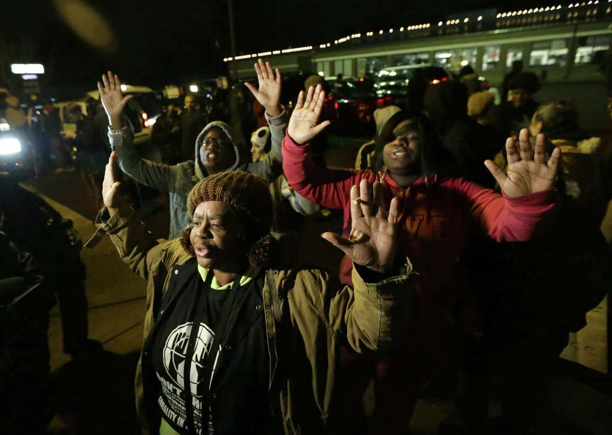 Barbara Jones, joined by other protesters, raises her hands, Monday, Nov. 24, 2014, in Ferguson, Mo., more than three months after an unarmed black 18-year-old man was shot and killed there by a white policeman in Ferguson. Ferguson and the St. Louis region are on edge in anticipation of the announcement by a grand jury whether to criminally charge Officer Darren Wilson in the killing of Michael Brown.