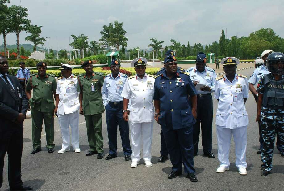 FILE - In this Monday, May. 26, 2014 file photo, Nigeria's chief of defense staff Air Marshal Alex S. Badeh, foreground third right, and other military chiefs wait to address the Nigerians Against Terrorism group during a demonstration calling on the government to rescue the kidnapped girls of the government secondary school Chibok, in Abuja, Nigeria. Nigerian military abuses caused the deaths of some 8,000 people in the fight against Boko Haram extremists, Amnesty International said Wednesday, June. 3, 2015  in a report naming senior officers it wants investigated for alleged war crimes.  (AP Photo/Olamikan Gbemiga File) Photo: AP / AP