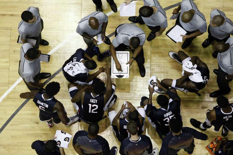 UConn coach Kevin Ollie, center, gives instructions to his players during a timeout during the title game of the Puerto Rico Tip-Off tournament on Sunday against West Virginia in San Juan. Photo: Ricardo Arduengo — The Associated Press  / AP